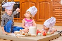 男孩和女孩和一个新出生的孩子与他们在厨师` s帽子坐厨房地板弄脏用面粉 免版税库存图片