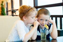 男孩和女孩喝饮料 图库摄影