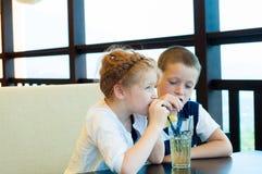 男孩和女孩喝饮料 免版税库存图片