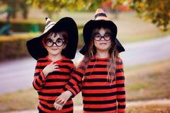 男孩和女孩在万圣夜服装的公园,获得乐趣 免版税库存照片