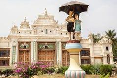 男孩和女孩在伞过去历史迈索尔大厦下,印度的卡纳塔克邦葡萄酒雕塑  库存图片