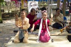 男孩和女孩在公园唱在lanna样式的一首歌曲,在泰国的北部 库存照片