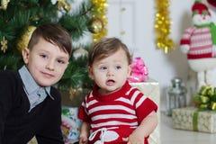 男孩和女孩在圣诞树附近 免版税库存图片