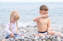 男孩和女孩在多岩石的海滩的建筑石料墙壁 库存图片
