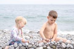 男孩和女孩在多岩石的海滩的建筑石料墙壁 图库摄影