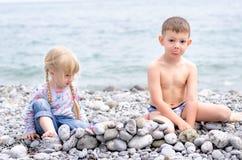 男孩和女孩在多岩石的海滩的建筑石料墙壁 库存照片