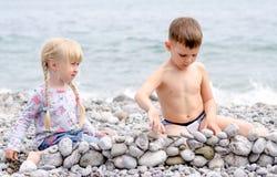 男孩和女孩在多岩石的海滩的建筑石料墙壁 免版税库存照片