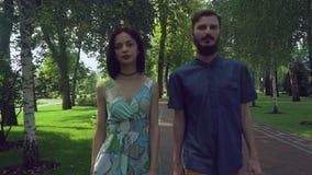 年轻男孩和女孩在步行附近去在公园 股票视频
