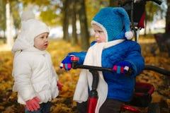 男孩和女孩在秋天公园 免版税库存图片