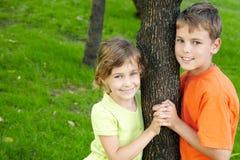 男孩和女孩在结构树的每个端突出 免版税库存图片