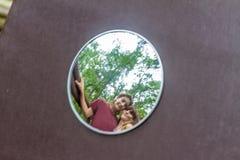 男孩和女孩在自然bac的圆的镜子反射了 免版税库存照片