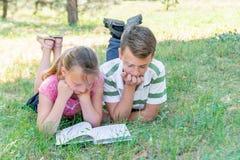 男孩和女孩在草参与教育,同学从一本课本一起读了,书说谎 库存图片