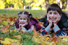 男孩和女孩在晴朗的秋天停放坐叶子 免版税库存照片