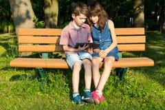 男孩和女孩坐一条长凳在公园,看 库存图片