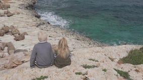 男孩和女孩坐在峭壁看的边缘 股票录像