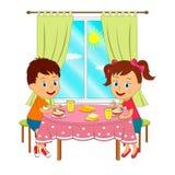 男孩和女孩坐在桌和吃上 免版税库存图片