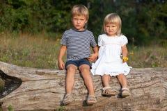 男孩和女孩坐日志 库存照片