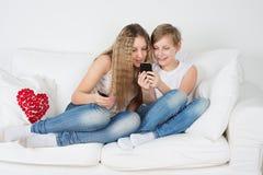 男孩和女孩坐有您的电话的长沙发 免版税库存照片