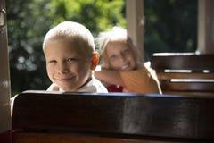 年轻男孩和女孩坐火车和微笑 免版税库存照片