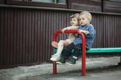 男孩和女孩坐长凳 库存照片
