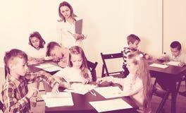 男孩和女孩基本的年龄的在图画教训 免版税库存照片