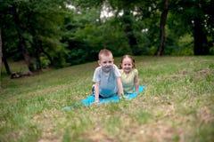男孩和女孩实践的瑜伽 免版税库存照片