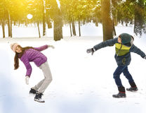 男孩和女孩投掷的雪球 库存照片