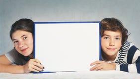 男孩和女孩拿着空白的长方形框架 免版税图库摄影