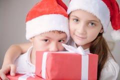男孩和女孩拿着箱子有礼物的圣诞老人帽子的 免版税库存图片
