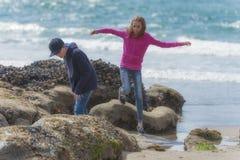 男孩和女孩探索浪潮水池 免版税图库摄影