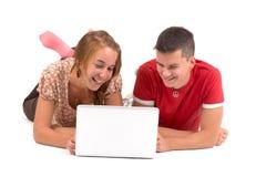 年轻男孩和女孩有便携式计算机的 免版税库存图片