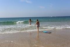 男孩和女孩有冲浪板的 图库摄影