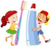 男孩和女孩有大牙刷和浆糊的 库存照片