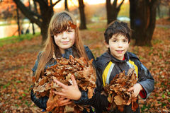 男孩和女孩有干燥叶子的对负准备好投掷 库存照片