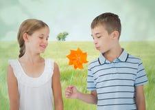 男孩和女孩有玩具风车的反对草甸 库存图片