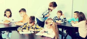 男孩和女孩有老师图画的 库存照片