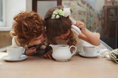 男孩和女孩有茶会在咖啡馆 免版税库存照片
