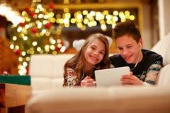 男孩和女孩有说谎和使用片剂的耳机的为基督 免版税库存照片