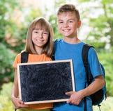 男孩和女孩有黑板的 免版税库存照片