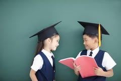 男孩和女孩毕业盖帽和学习的 免版税库存图片