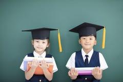 男孩和女孩毕业盖帽的在教室 免版税库存图片
