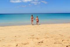 男孩和女孩海滩的一起去海,费埃特文图拉岛加那利群岛 图库摄影