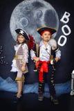 男孩和女孩海盗服装的 日历概念日期冷面万圣节愉快的藏品微型收割机说大镰刀身分 库存图片