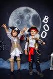 男孩和女孩海盗服装的 日历概念日期冷面万圣节愉快的藏品微型收割机说大镰刀身分 免版税库存图片
