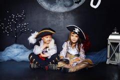 男孩和女孩海盗服装的 日历概念日期冷面万圣节愉快的藏品微型收割机说大镰刀身分 库存照片