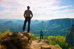 男孩和女孩游人在峭壁和认为停留 梦想的老保守风景,在下面美丽的谷的蓝色有薄雾的日出 免版税库存图片