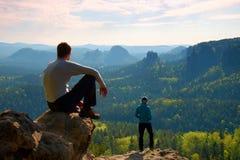 男孩和女孩游人在峭壁和认为停留 梦想的老保守风景,在下面美丽的谷的蓝色有薄雾的日出 图库摄影