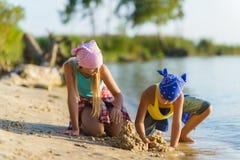 男孩和女孩演奏并且修造在海滩的沙子城堡 库存图片