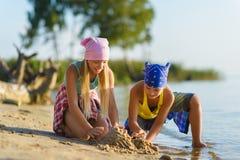 男孩和女孩演奏并且修造在海滩的沙子城堡 免版税库存图片