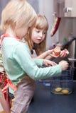 男孩和女孩烹调某事 免版税库存图片